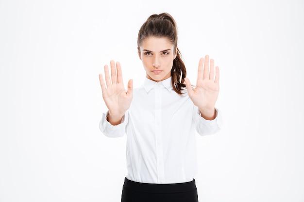 Bella giovane donna d'affari seria che mostra il gesto di arresto con entrambe le mani