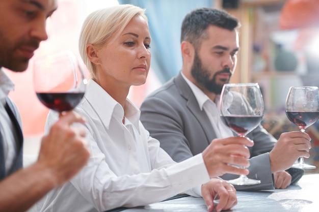 Grave donna bionda guardando il vino rosso in bokal mentre valuta il colore della bevanda tra i suoi colleghi