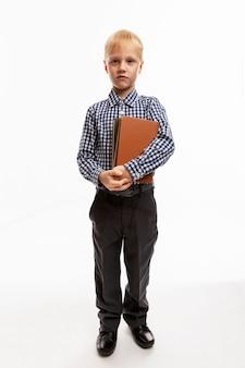 Un bambino serio di 6 anni è in piedi con un libro in mano. di nuovo a scuola