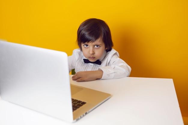 Uomo d'affari serio bambino ragazzo in una camicia bianca e farfallino si siede a un computer portatile a una scrivania in un ufficio giallo
