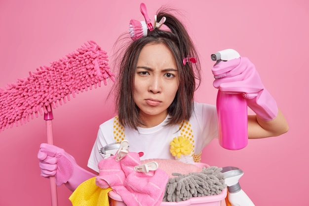 La donna asiatica bruna seria ha uno sguardo attento alla telecamera usa spray per rimuovere la polvere sui mobili tiene il mop aggrotta le sopracciglia pose vicino al cesto della biancheria isolato sul muro rosa