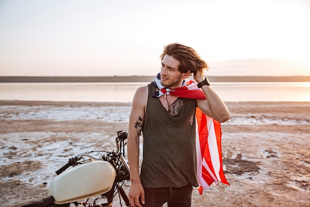 Uomo brutale serio che indossa mantello della bandiera americana e casco d'oro in piedi vicino a una moto nel deserto