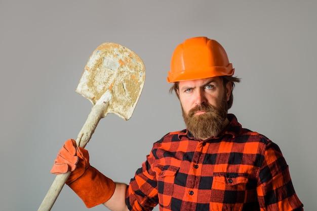 Il costruttore serio in elmetto con la pala pubblicizza l'operaio di riparazione con il costruttore di vanga nel lavoro