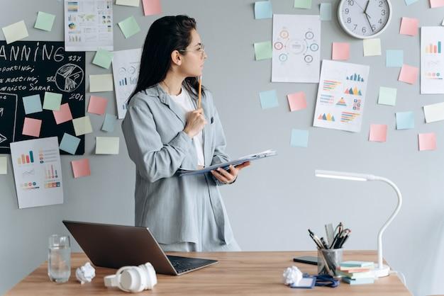 Una seria ragazza d'affari sta studiando attentamente un grafico appeso al muro