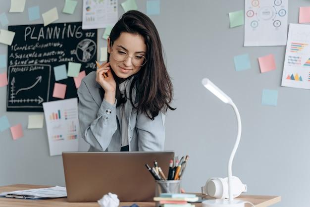 Signora seria di affari che lavora al computer portatile in ufficio