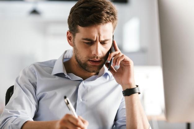 Uomo serio di affari che parla dallo smartphone e scrive qualcosa mentre era seduto al tavolo in ufficio