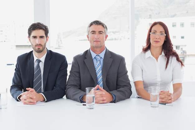 Gente di affari seria che si siede insieme