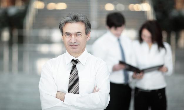 Uomo d'affari serio sullo sfondo del team aziendale. concetto di business