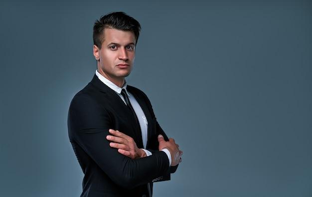 Uomo d'affari serio in un abito nero isolato su sfondo grigio. bell'uomo in piedi con le braccia incrociate.
