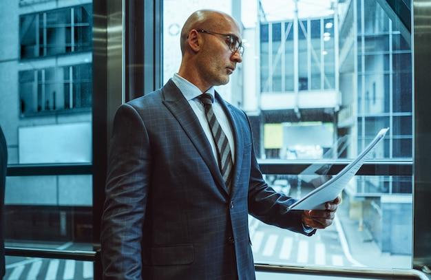 Uomo d'affari serio legge che tiene documento cartaceo. il caucaso di mezza età esamina il contenuto degli affari