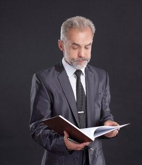 Serio uomo d'affari firma un documento di lavoro.isolato su fondo nero.