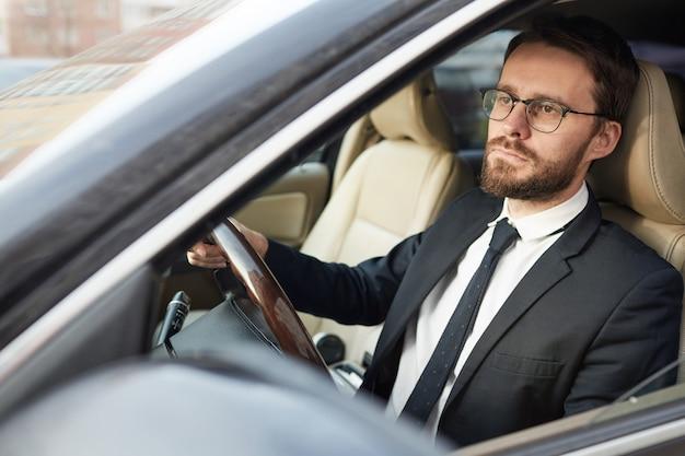 Uomo d'affari serio che si siede in macchina