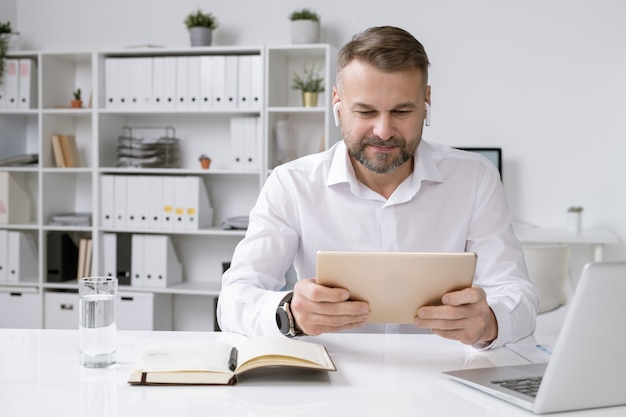Uomo d'affari serio con il touchpad che guarda la formazione video in linea, la conferenza o il webinar dalla scrivania in ufficio