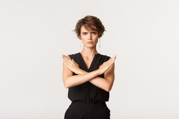 La donna di affari seria che mostra il gesto trasversale e che aggrotta le sopracciglia, dice di fermarsi, dicendo no o vietare qualcosa, in piedi sopra il bianco.