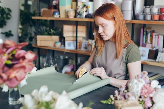 Grave donna giovane rossa impegnata in grembiule in piedi dal bancone e taglio carta da imballaggio per imballaggi di fiori nel negozio di fiori