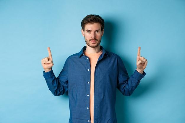 Uomo caucasico serio con la barba che punta le dita verso lo spazio vuoto, che mostra il logo e che guarda l'obbiettivo, in piedi su sfondo blu.