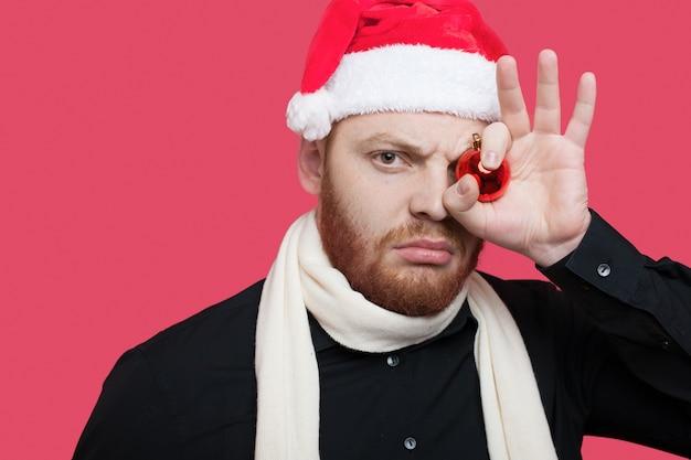 Un uomo caucasico serio con barba e cappello della santa si copre gli occhi con una palla di decorazione natalizia in posa su un muro rosso con spazio libero