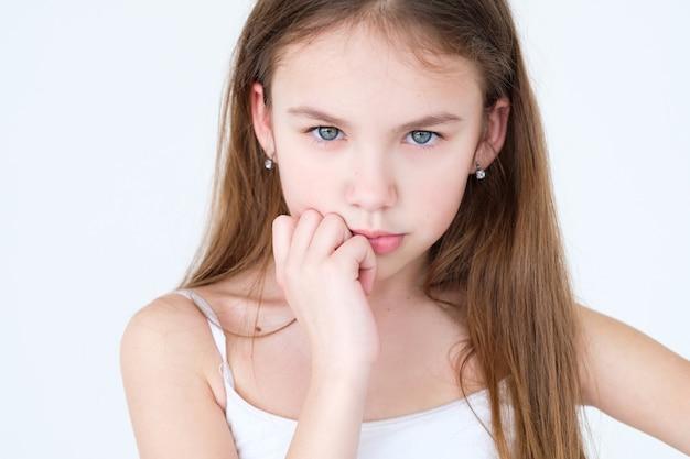 Bambino serio che pensa con la mano sotto il mento sulla parete bianca.