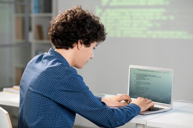 Studente intelligente serio che si piega dalla scrivania davanti al computer portatile mentre prepara la presentazione del suo progetto per la conferenza dopo le lezioni