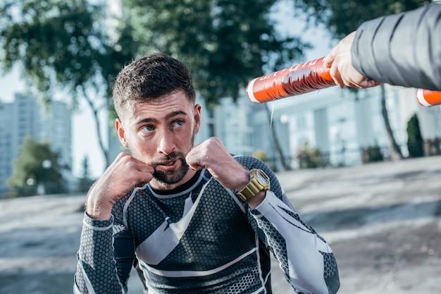 Grave pugile barbuto concentrato che alza i pugni mentre si allena mma con i bastoni da boxe