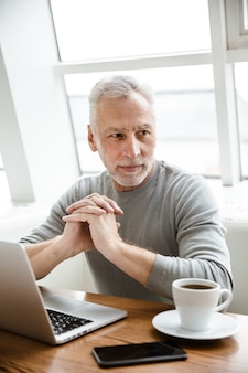 Un uomo d'affari senior maturo concentrato serio si siede in caffè facendo uso del computer portatile.