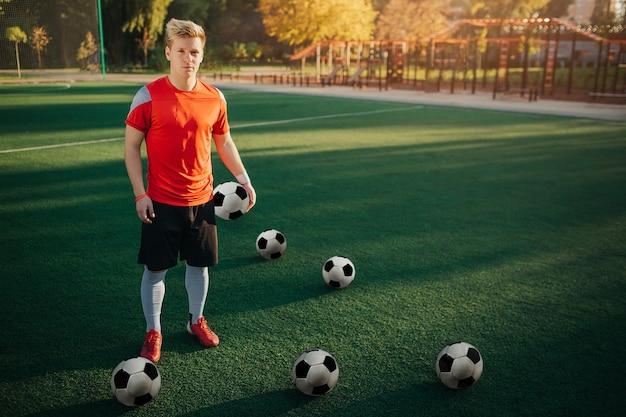 Il giovane giocatore di football americano serio e concentrato sta sul prato inglese
