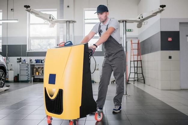 Il giovane serio e concentrato in uniforme sta alla macchina di pulizia e si appoggia su di esso.