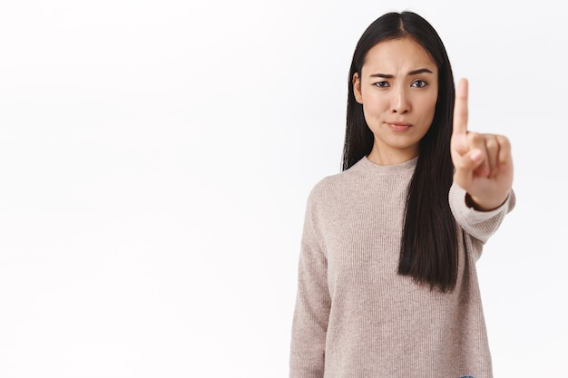 La femmina asiatica seria e sicura di sé proibisce e avverte l'amico, chiede di fermarsi, allunga il dito in avanti nel tabù, gesto di rifiuto, sorrisetto scettico e dispiaciuto, non mi piace quello che sta succedendo