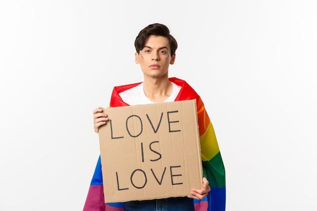 Uomo gay serio e fiducioso che indossa la bandiera arcobaleno lgbt, con cartello per la parata dell'orgoglio, in piedi sopra il bianco.