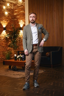Uomo serio e fiducioso bello con la moderna giacca verde in piedi in appartamento loft