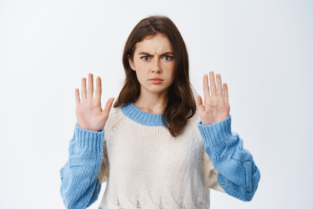 Donna seria e fiduciosa accigliata, alzando le mani nel gesto di blocco e dire no, disapprovare le cattive azioni, cercando di avvertire o rifiutare, in piedi contro il muro bianco