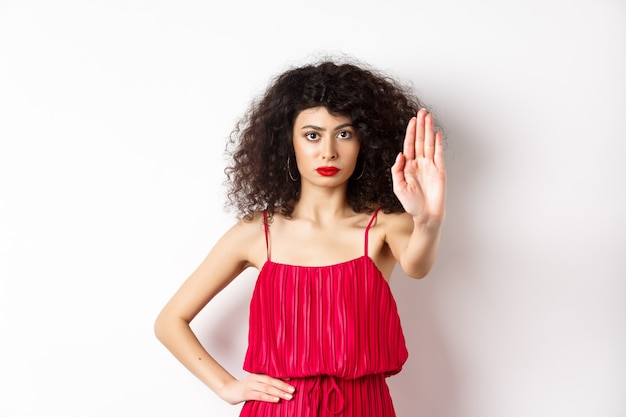 Donna seria e sicura di sé in abito rosso e trucco stendere la mano, dire di fermarsi, proibire e proibire qualcosa, in piedi su sfondo bianco.