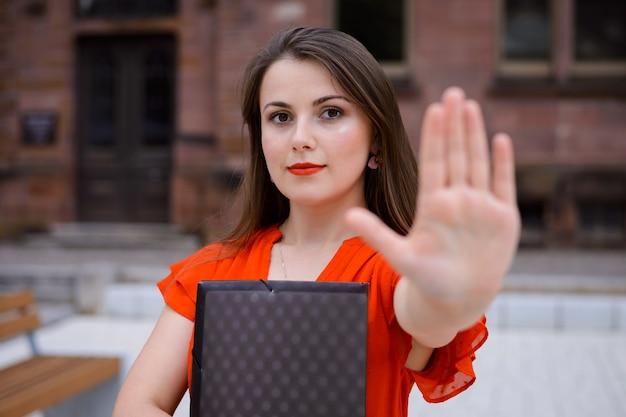 Grave donna sicura di sé che mostra un segnale di stop come protesta e disapprovazione