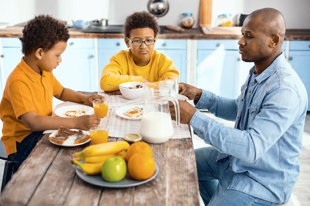 Conversazione seria. allegro giovane padre seduto al tavolo della cucina con i suoi figli e li rimprovera per un cattivo comportamento mentre tengono il broncio