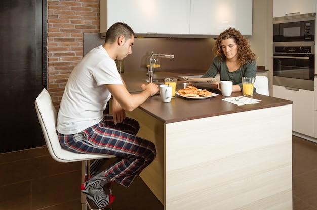 Coppia seria che legge notizie in una colazione a casa
