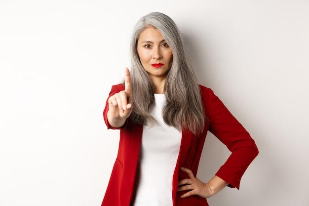 Donna d'affari asiatica seria e delusa che mostra il gesto di arresto, agitando il dito in segno di disapprovazione, rifiutando qualcosa di brutto, in piedi su sfondo bianco