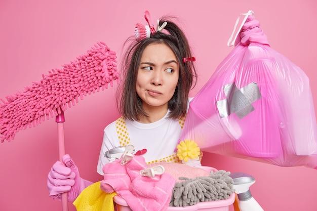 La governante asiatica seria dispiaciuta con mollette sui capelli guarda attentamente il sacchetto della spazzatura impegnato a fare il bucato per pulire il pavimento con la scopa fa i lavori domestici isolati su sfondo rosa. concetto di cameriera