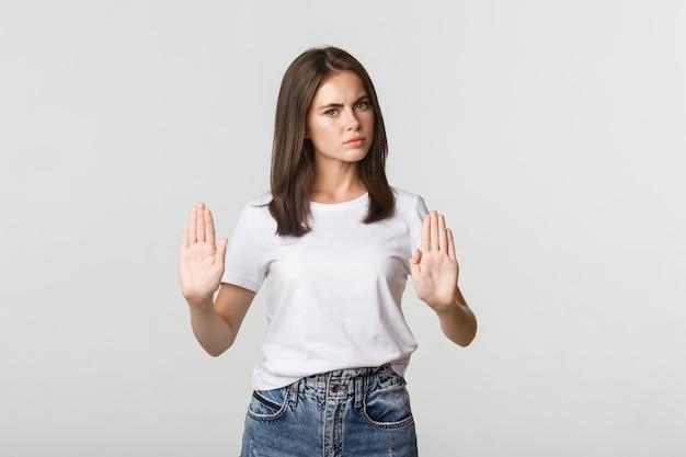 Giovane donna scontenta seria che mostra il gesto di arresto, dicendo no.