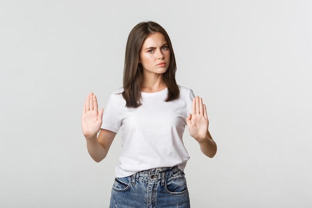 Grave giovane donna scontenta che mostra il gesto di arresto