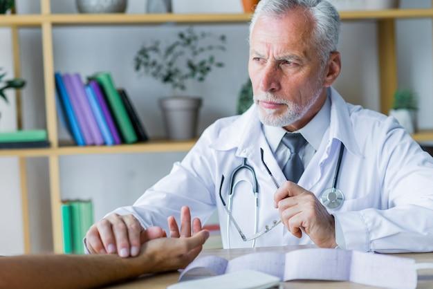 Medico serio che controlla impulso del paziente