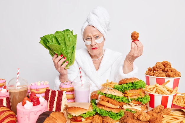 Una donna europea anziana seria sceglie tra cibo sano e cibo malsano