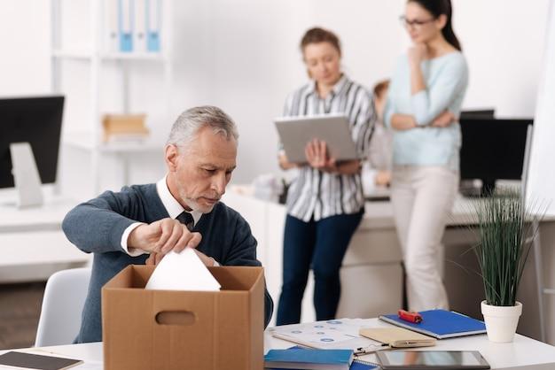 Grave uomo anziano chinando la testa, guardando il suo tavolo mentre si prendono i documenti dalla grande scatola