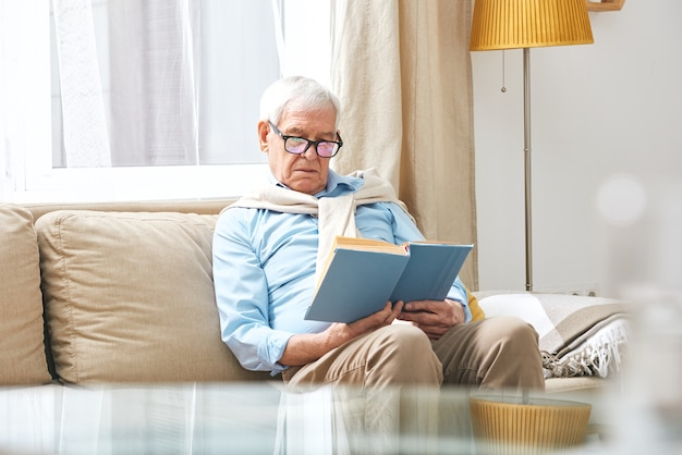 Uomo anziano serio in occhiali seduto sul divano e leggendo un libro interessante in soggiorno