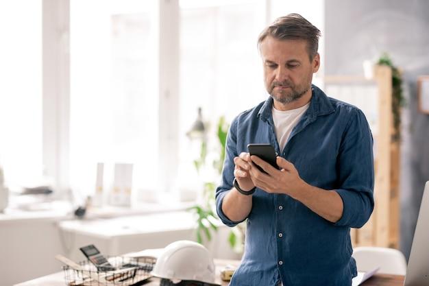 Ingegnere serio in abbigliamento casual che scorre i contatti nel suo smartphone mentre lavora in ufficio