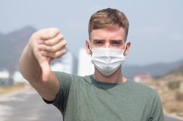 Uomo europeo serio, giovane ragazzo in maschera medica sterile protettiva sul viso, mostra il pollice verso il basso, non piace il gesto. concetto di coronavirus
