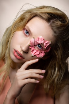 Faccia seria. modello professionale biondo dagli occhi azzurri in posa con petali di fiori vicino all'occhio