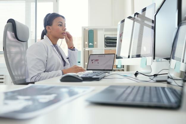 Medico femminile serio in cuffie che esaminano il monitor del computer che ha conferenza in linea all'ufficio