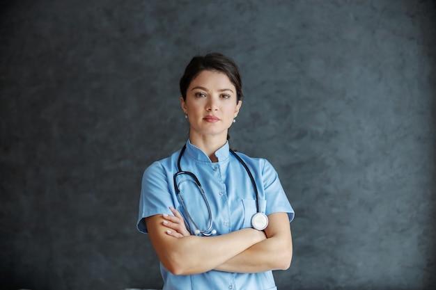Medico femminile serio con lo stetoscopio intorno al collo in piedi con le braccia incrociate