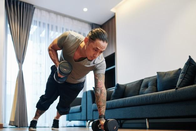 Uomo di razza mista in forma seria che fa esercizio di fila di manubri sollevando pesi con manubri nel suo appartamento