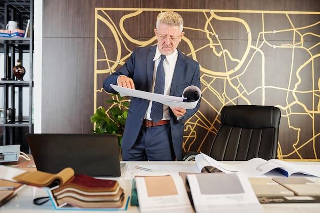 Grave uomo di mezza età accigliato in piedi al tavolo con documenti di ingegneria e campioni di tessuto